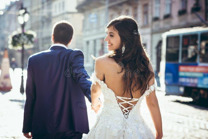 Brudgummen är ledande vid handen hans förtjusande le brunettbrud i klänningen med kalt tillbaka längs stadgatan _ royaltyfri fotografi