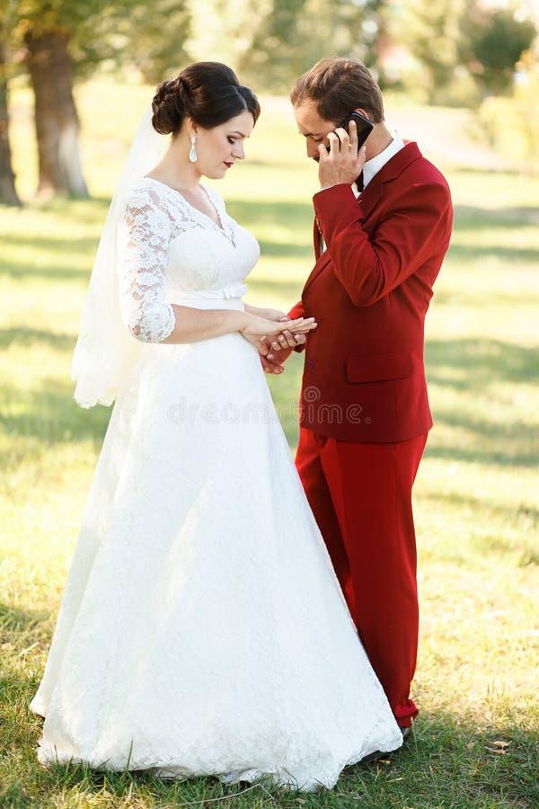 Brudgummen är upptagen samtal på telefonen, väntande missnöje för brud Akut appell, patiens på bröllop royaltyfria foton