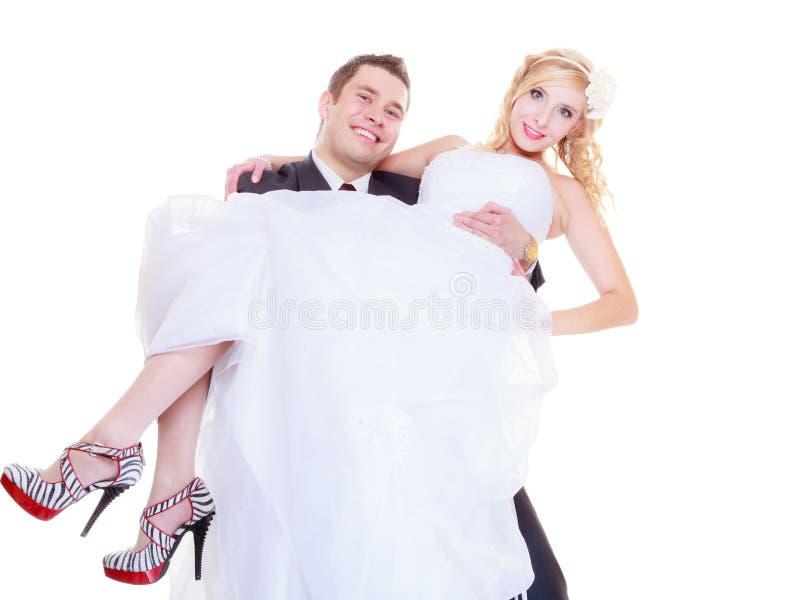 Brudgummen bär bruden i hans armar arkivfoto