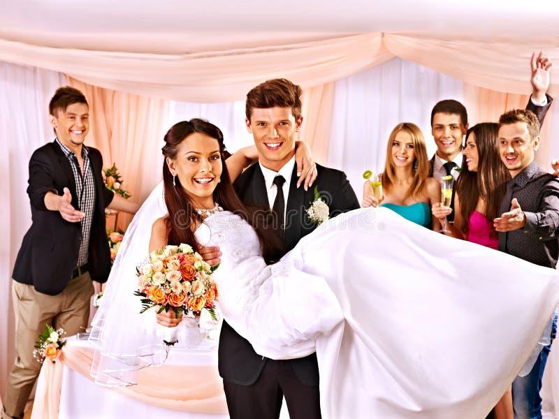 Brudgummen bär bruden på hans händer arkivbild