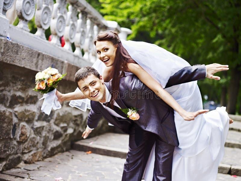 Brudgummen bär hans brud över baksida. arkivbild
