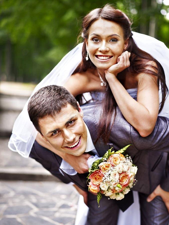 Brudgummen bär hans brud över baksida. royaltyfri fotografi