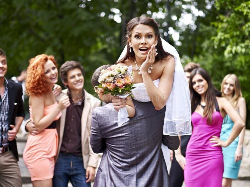 Brudgummen bär hans brud över skuldra. royaltyfria foton