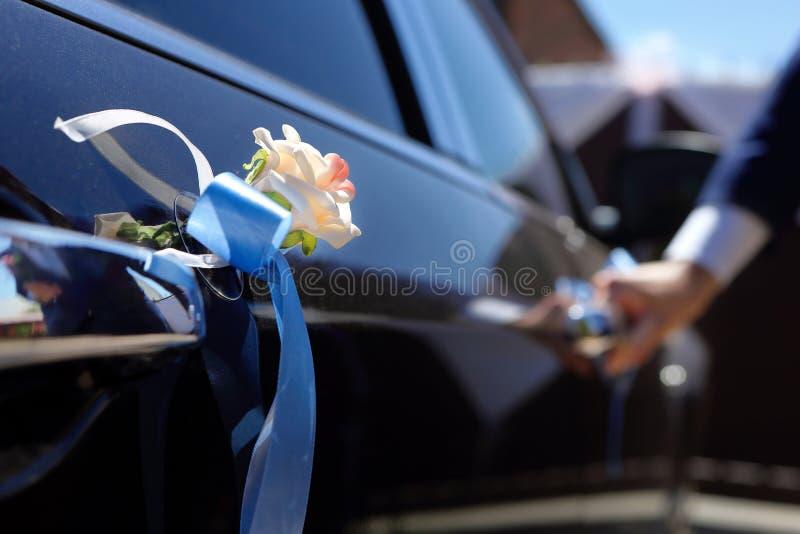 Brudgummen får in i bilen royaltyfri foto
