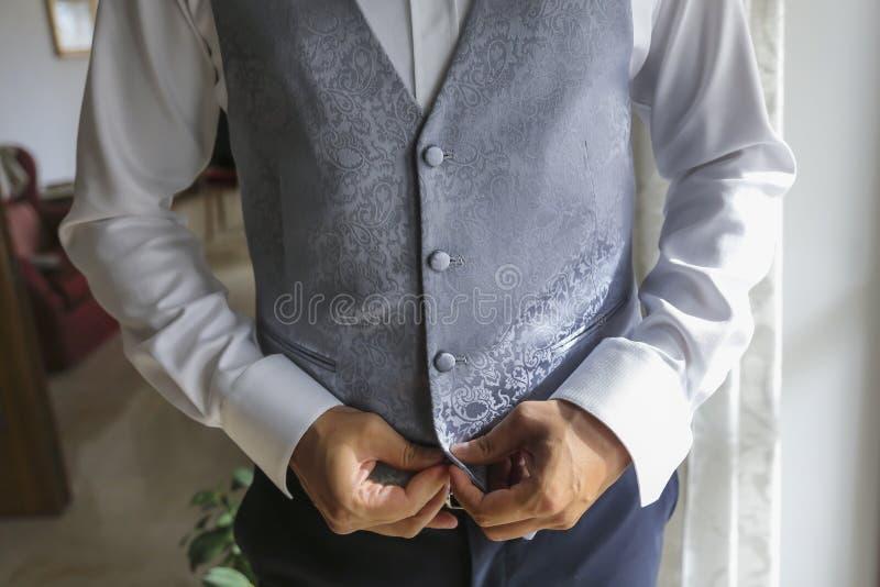 Brudgummen förbereder sig för bröllopet med waistcoattait fotografering för bildbyråer