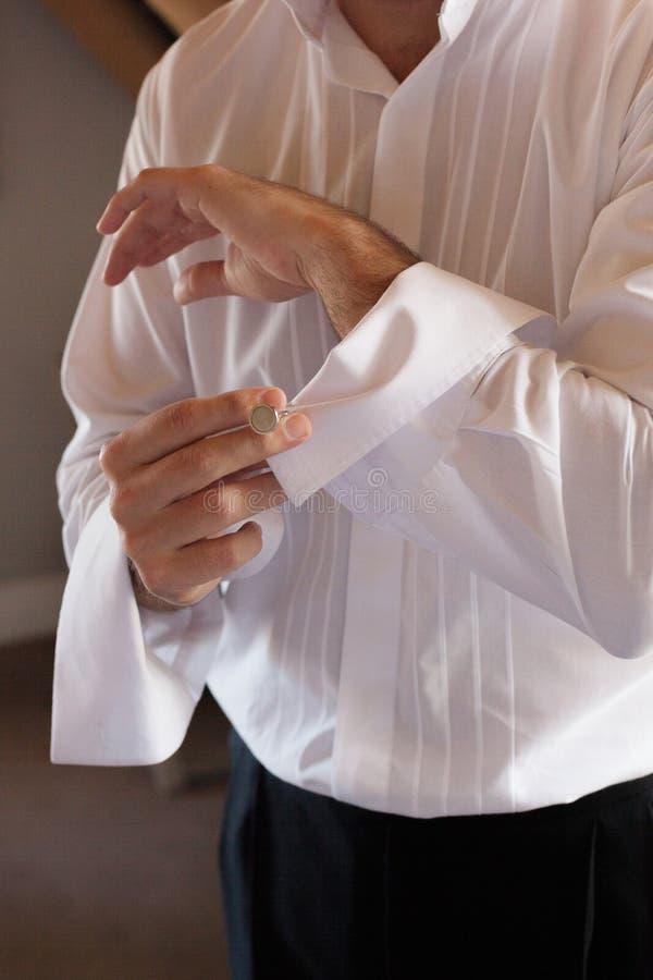 Brudgummen gör upp hans cufflinks royaltyfria bilder