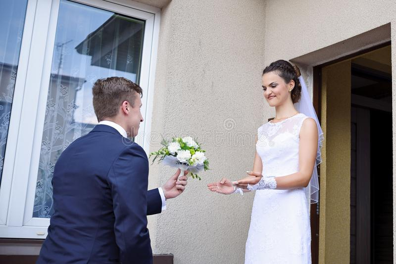 Brudgummen ger bruden blommor royaltyfri bild