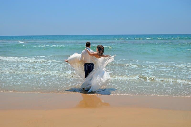 Brudgummen i en dräkt bär på hans händer bruden i en bröllopsklänning i vattnet av Indiska oceanen Gifta sig och bröllopsresa royaltyfria bilder