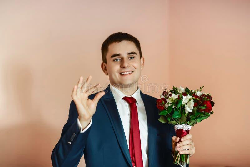 Brudgummen i en dräkt rymmer i hans hand vigselringarna och en gifta sig bukett arkivfoto