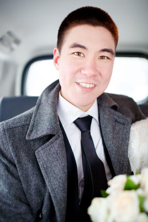 Brudgummen i ett vinterlagsammanträde i bilen med bröllopbuketten i händer Positiv stående som ser in i kameran royaltyfria bilder