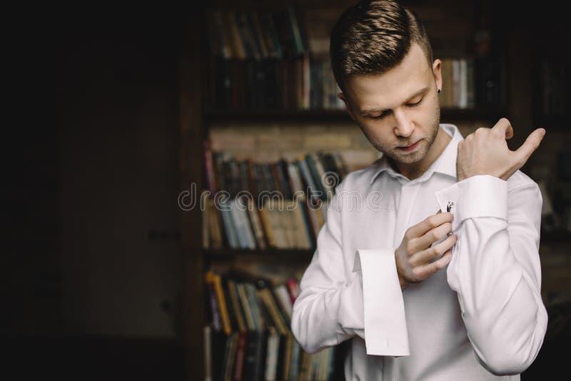 Brudgummen justerar hans omslag, brudgum i ett omslag, morgonen av arkivfoto
