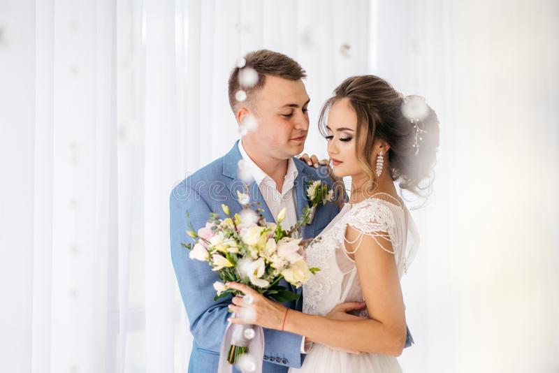 Brudgummen kramar bruden i rummet royaltyfria foton