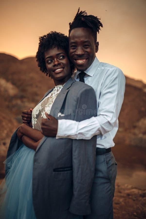 Brudgummen kramar hans brud som är iklädd hans omslag i kanjon på solnedgången arkivfoton