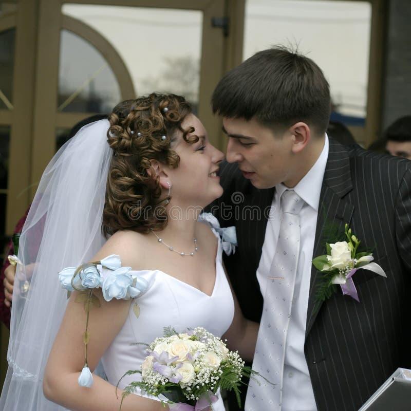 Brudgummen kysser bruden royaltyfria foton