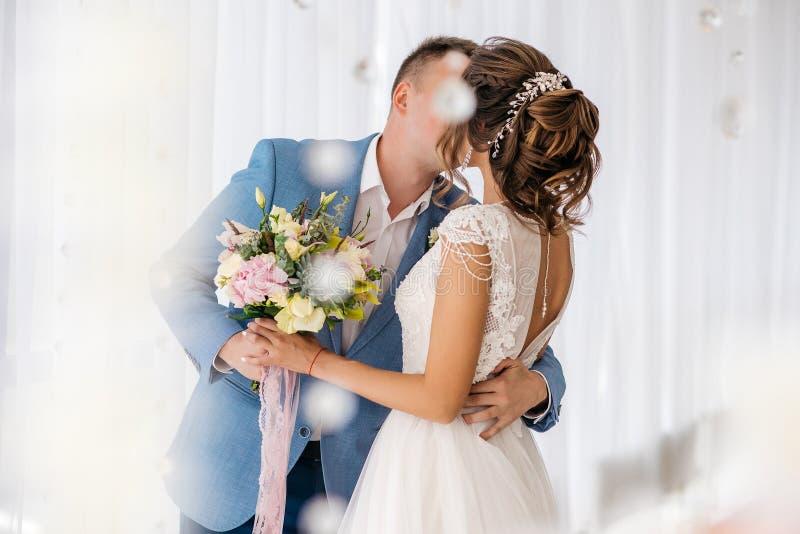 Brudgummen kysser bruden i rummet fotografering för bildbyråer