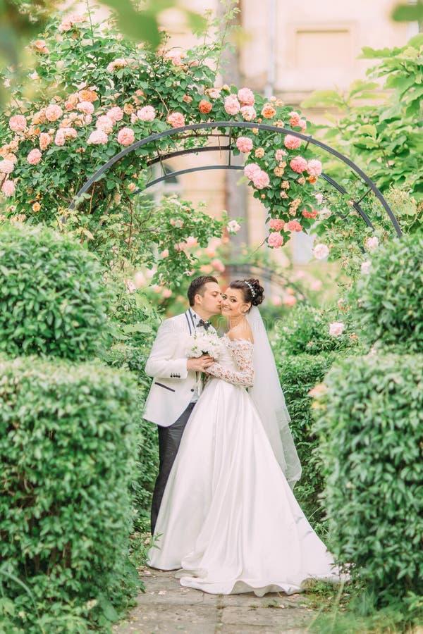 Brudgummen kysser den charmiga bruden i kinden under rosbågen fotografering för bildbyråer