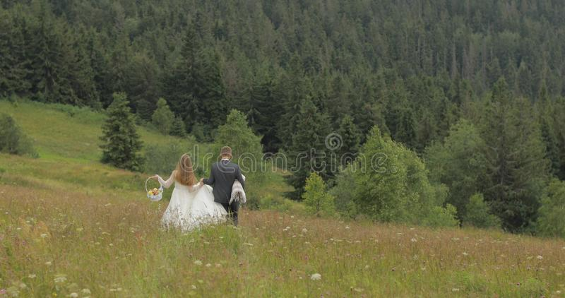 Brudgummen med bruden går för en picknick på kullar för ett berg binder crystal smycken f?r parcravaten br?llop familj arkivfoton