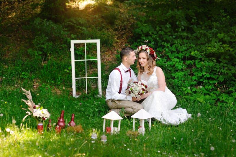 Brudgummen och bruden sitter på gräset i parkera fotografering för bildbyråer