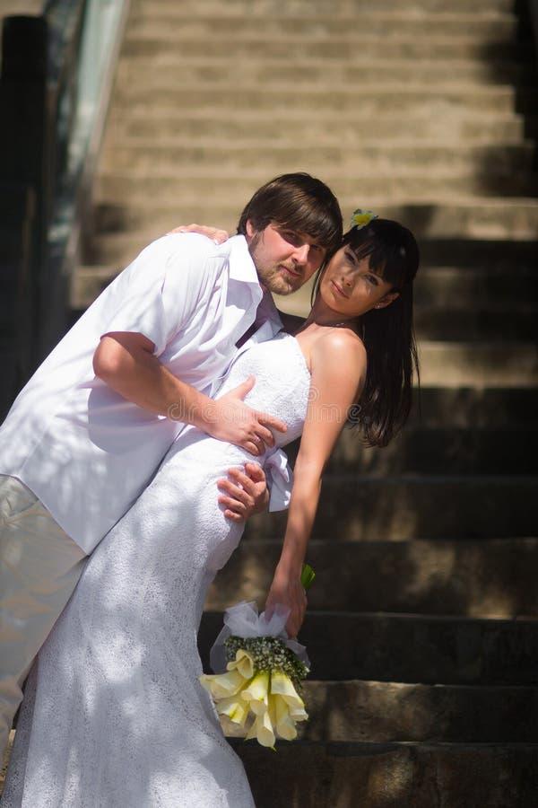 Brudgummen omfamnar brudanseendet på stenmomenten i den öppna luften royaltyfri bild