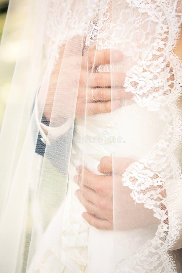 Brudgummen omfamnar brudar royaltyfria bilder