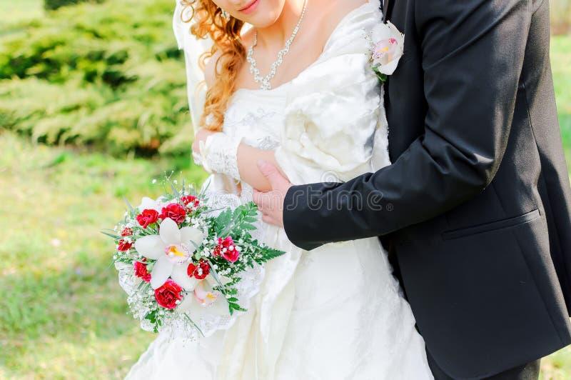 Brudgummen omfamnar bruden royaltyfria bilder