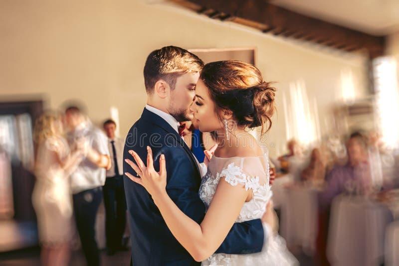 Brudgummen omfamnar bruden under bröllopdansen arkivfoto