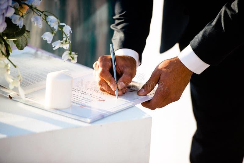 Brudgummen på den gifta sig ceremonin sätter hans häfte på dokumentet royaltyfri bild