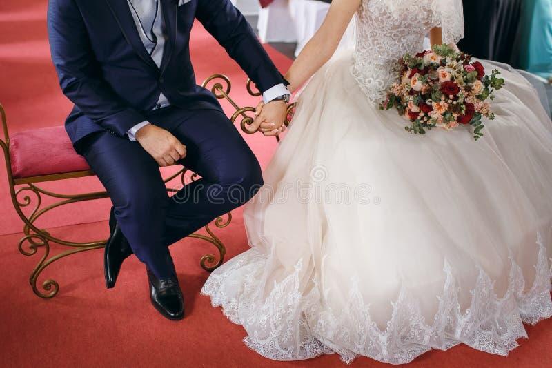 Brudgummen rymmer brudens händer under den gifta sig ceremonin, det spanska bröllopet arkivbild