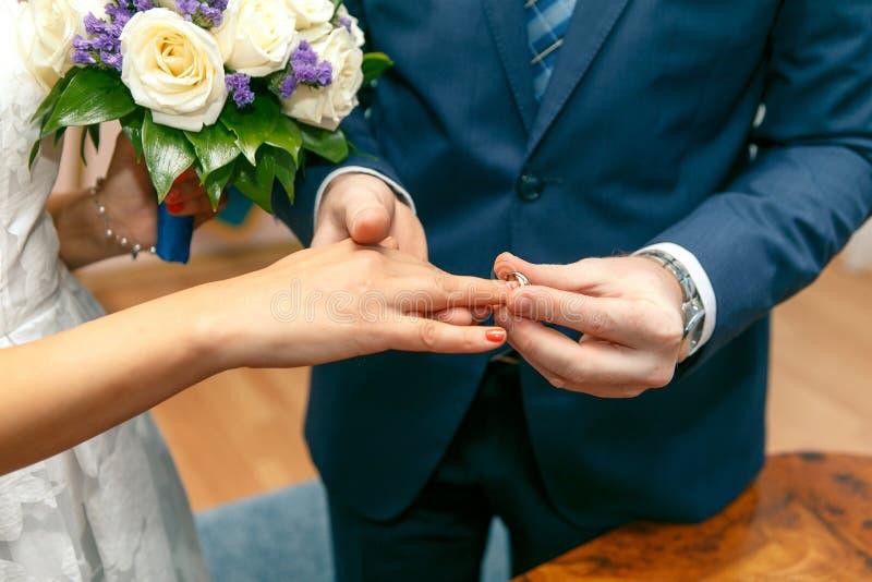Brudgummen sätter på en förlovningsring på fingret av bruden royaltyfri foto