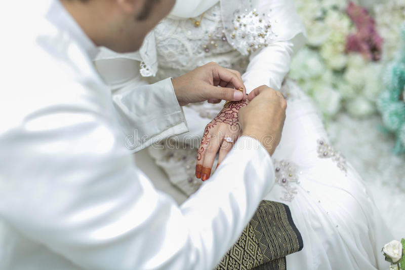 Brudgummen satte en vigselring till brudhanden Grund DOF Sel royaltyfri fotografi