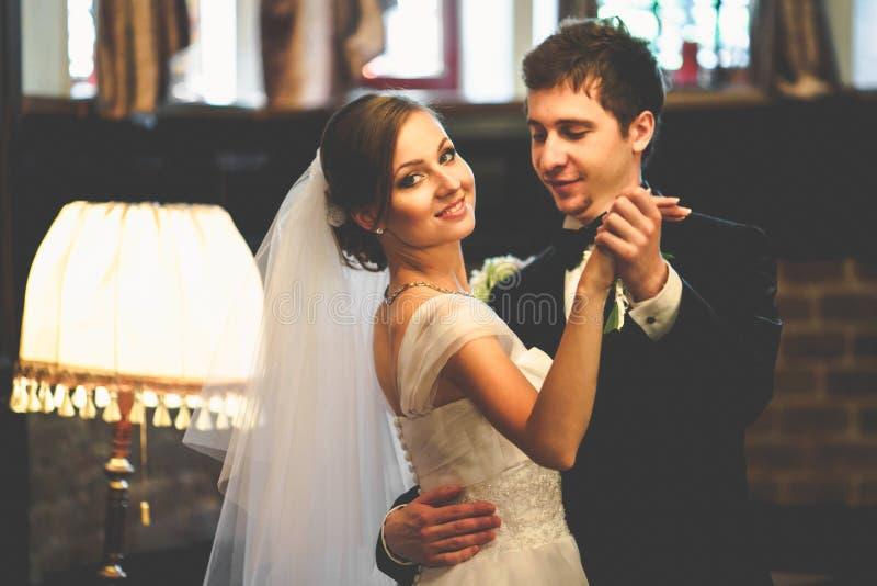 Brudgummen ser stolt dans med bruden i tappningkorridor royaltyfri foto