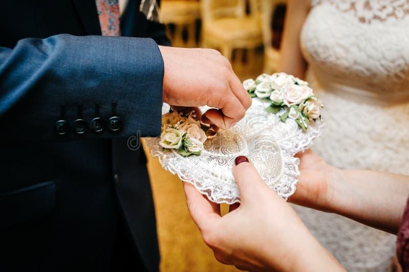 Brudgummen tar vigselringar från enformad kudde arkivfoton