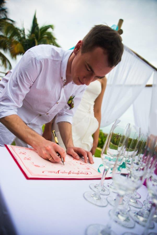 Brudgummen undertecknar dokument på registrering av förbindelsen i den öppna luften Ett ungt par undertecknar bröllopdokumenten M arkivfoton