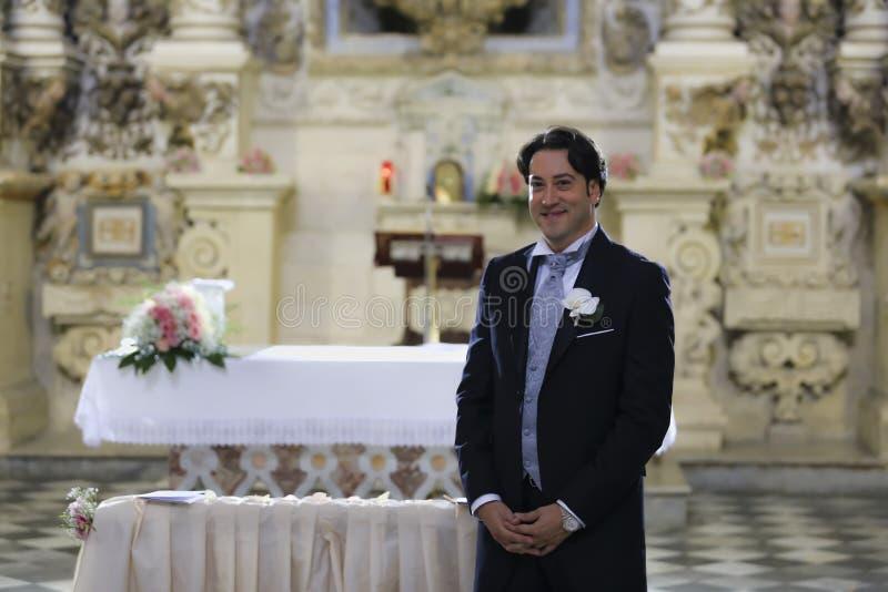 Brudgummen väntar på bruden på det kyrkliga altaret royaltyfri foto