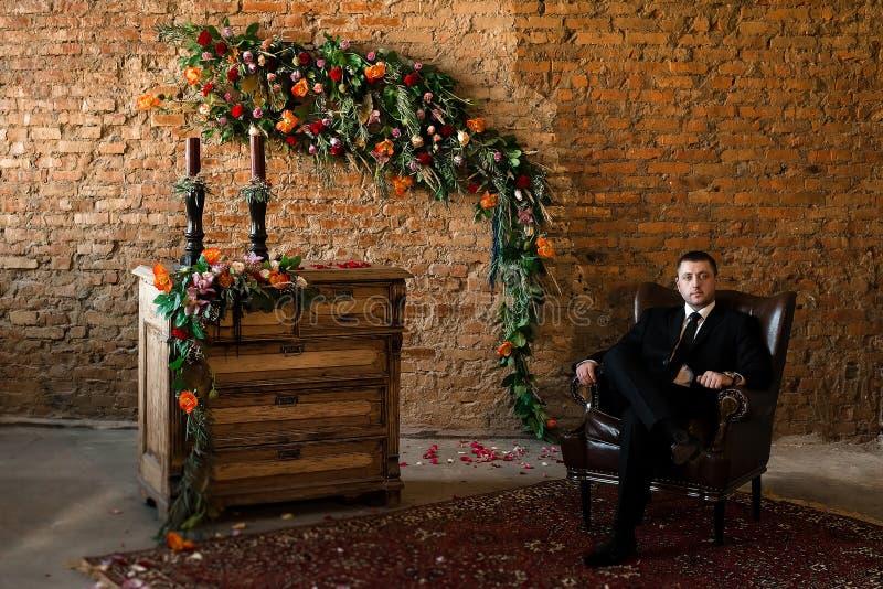 Brudgumsammanträde i en stor stol säkert royaltyfria foton