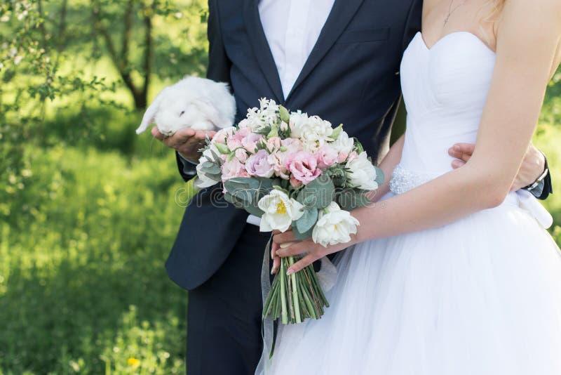 Brudinnehav i henne händer en delikat bröllopbukett med vita och rosa tulpan och rosa små rosor Brudgum som rymmer en vit gullig royaltyfria foton