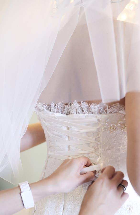 Download Brudkorsetthänder Som Drar åt Till Arkivfoto - Bild av lace, bröllopsresa: 19776964