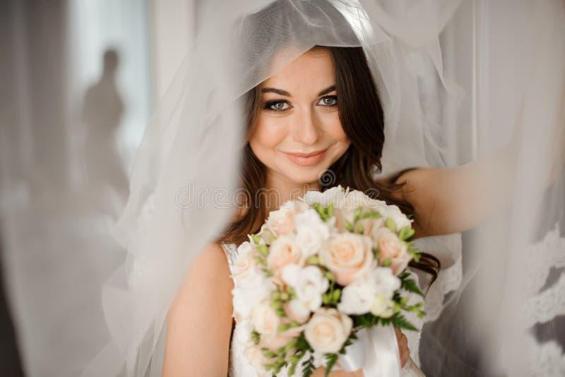Brudmorgonförberedelse Lyckligt och le bruden i en vit skyla med en bröllopbukett fotografering för bildbyråer