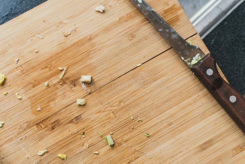 brudna drewniana tnąca deska z nożem Cebule ciąć na tnącej desce szczątki greenery na drewnianym tle obraz stock