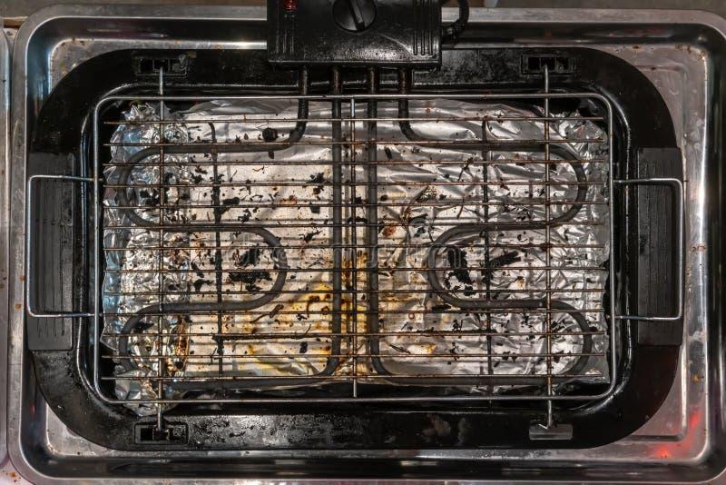 Brudna elektryczna grill kuchenka w metal tacy w przemysł kuchni zdjęcie royalty free