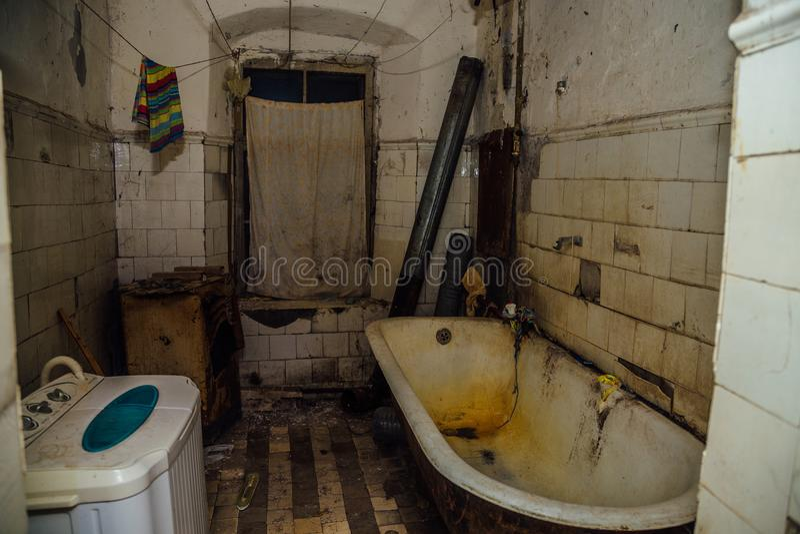 Brudna upaćkana łazienka jest w biednym mieszkaniu w starym nagłego wypadku domu zdjęcie royalty free