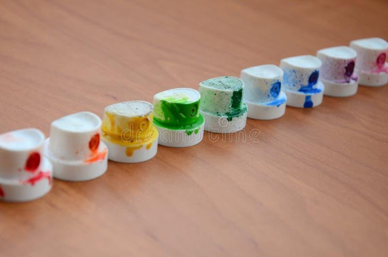 Brudnawi stubarwni nozzles od farby natryskownicy wykładają up na drewnianym stole Uliczny sztuki concep fotografia stock
