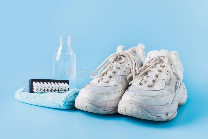 Brudne białe trampki ze specjalnym narzędziem do czyszczenia na niebiesko zdjęcie royalty free