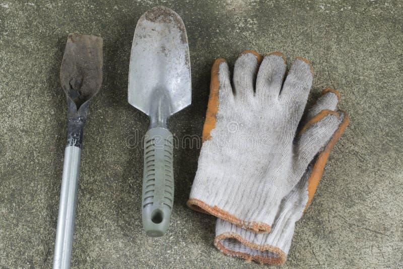 Brudne i stare ogrodowe łopaty i rękawiczki na betonowej podłoga obraz stock
