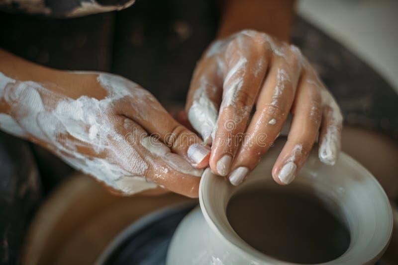 Brudne ręki w białej glinie, ceramicznym kole z pucharem lub słoju, Garncarka przy pracą, kobiety ` s ręki obrazy stock