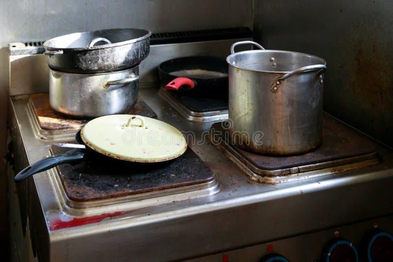 Brudni garnki i niecki umieszczają na stali nierdzewnej elektrycznej kuchence na galerze na statku obraz stock