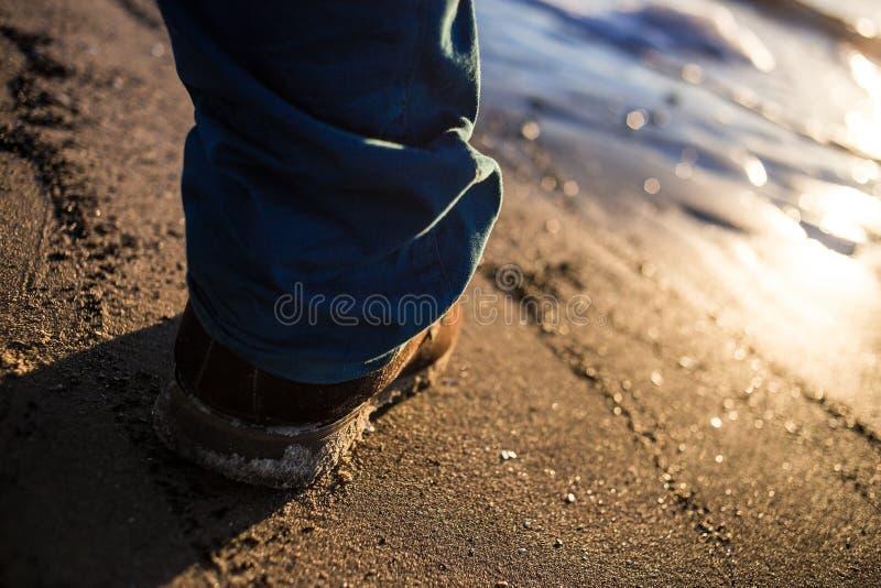 Brudni Męscy buty na textured dennych piaska kontrasta błękita spodniach zdjęcie royalty free