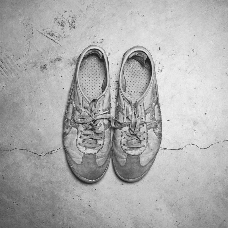 Brudni starzy buty na betonowej podłoga zdjęcia stock