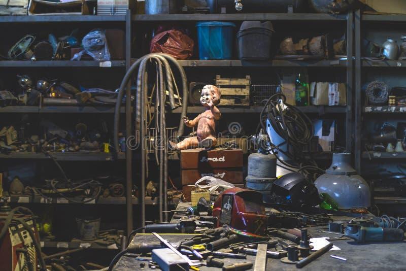 Brudny plastikowy dziecko - lala pozuje inside metalu sklep zdjęcie royalty free