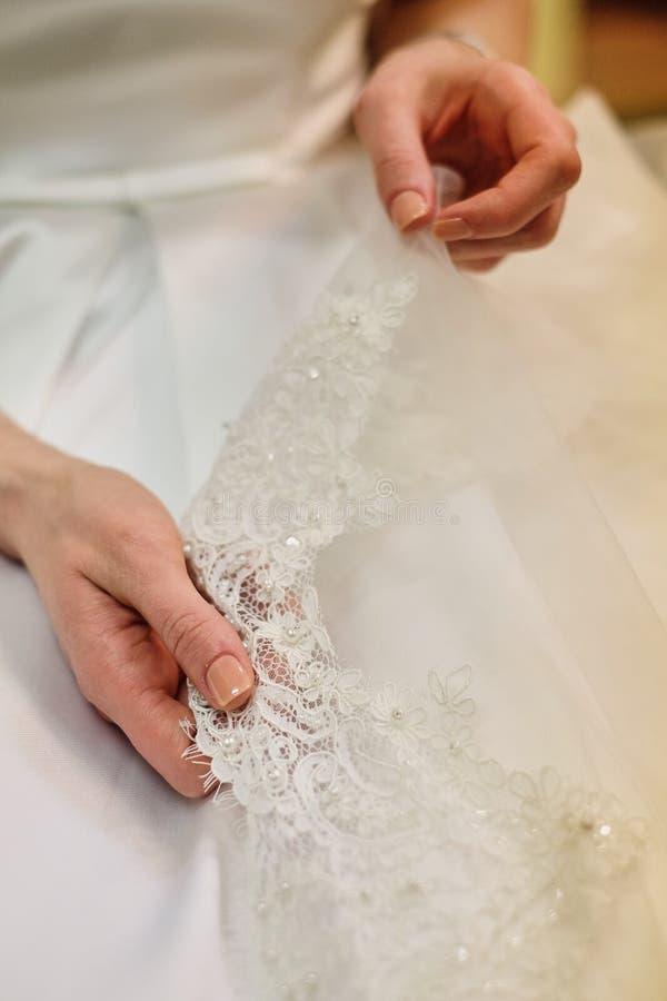 Bruds hand som trycker på detaljer av hennes bröllopsklänning Enkel fransk manikyr, händer trycker på kanten av skyler royaltyfria bilder